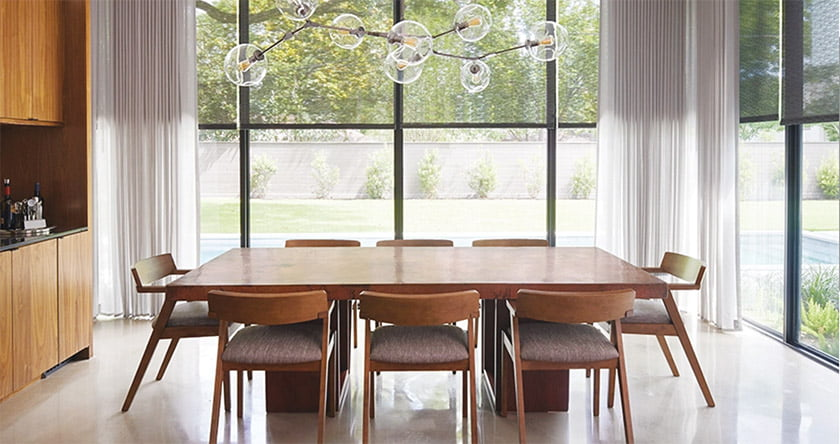 A dining room combines Chilewich solar shades with fade-resistant drapery panels by  Sunbrella; both are available through The Shade Store.