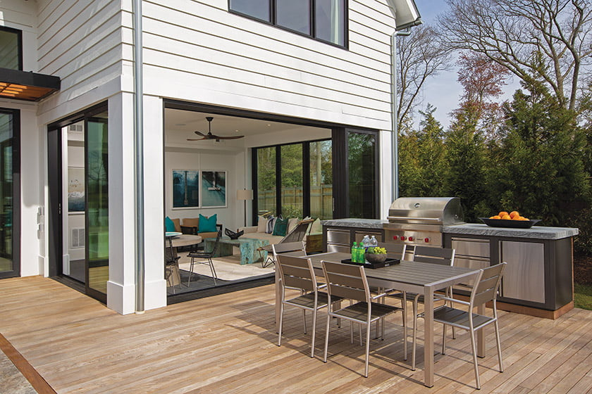 Sliders create an opening between the sunroom and the outdoor dining area, complete with a Wolf grilling station.