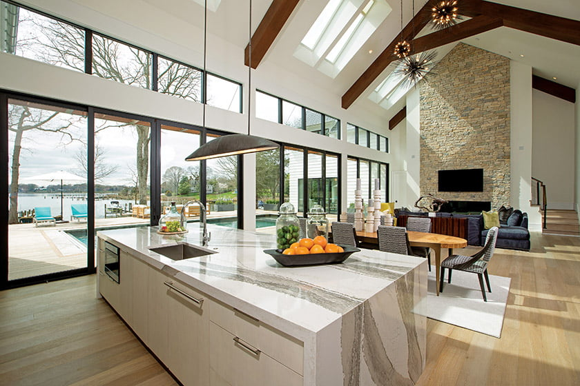 The great room holds living and dining areas and the kitchen; the quartz island countertop reflects a watery surface.