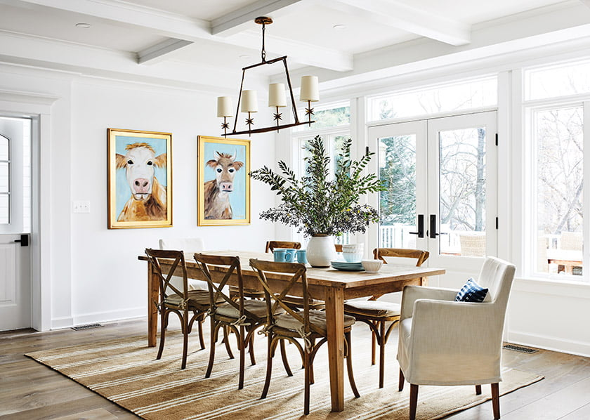 An antiqued-brass chandelier from Visual Comfort hangs over an RH table in the dining area.
