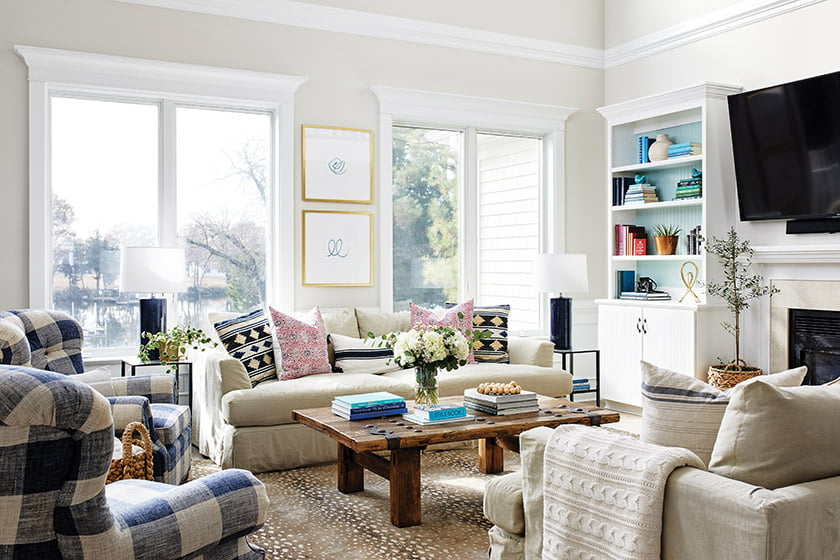 In the family room, sofas from Arhaus and a Stark carpet get a punch of color from throw pillows and chairs in a blue check.