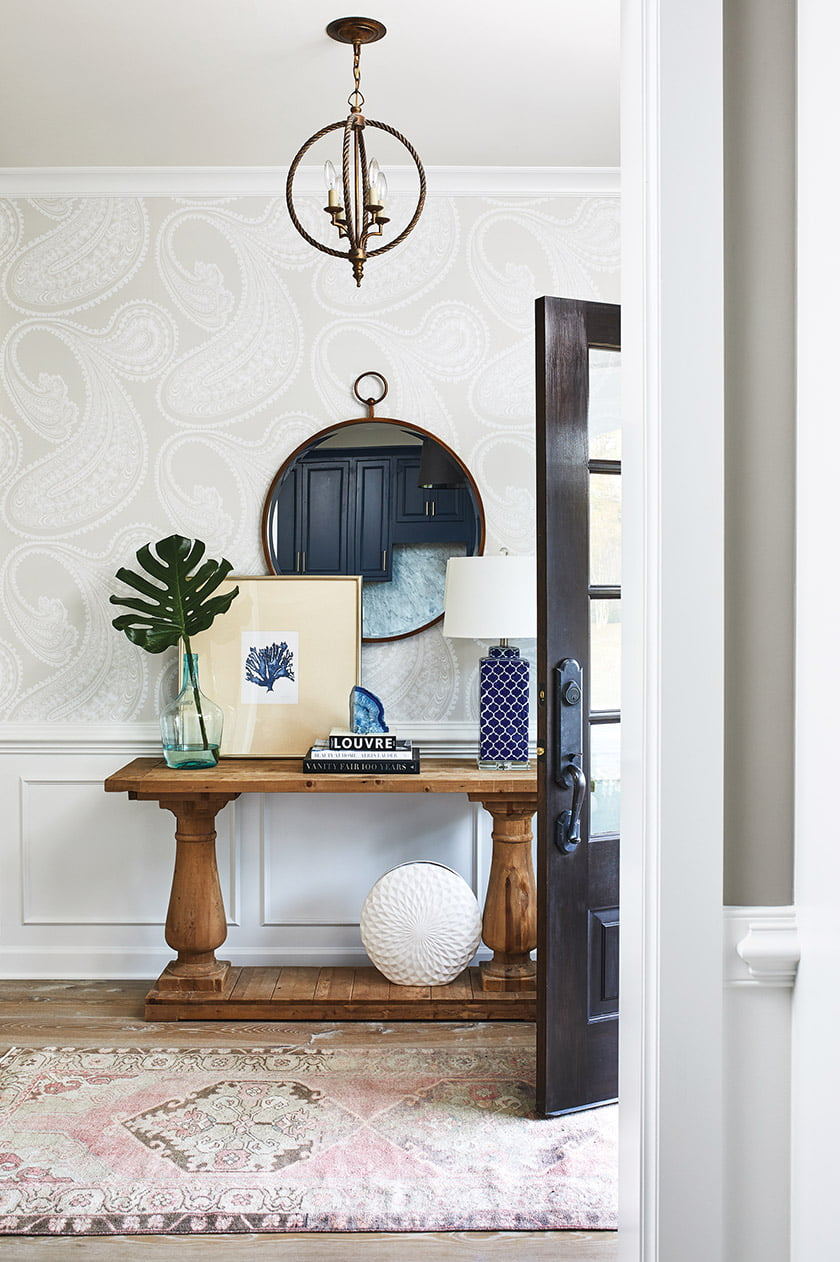 The entryway features Cole and Son's Rajapur wallpaper.
