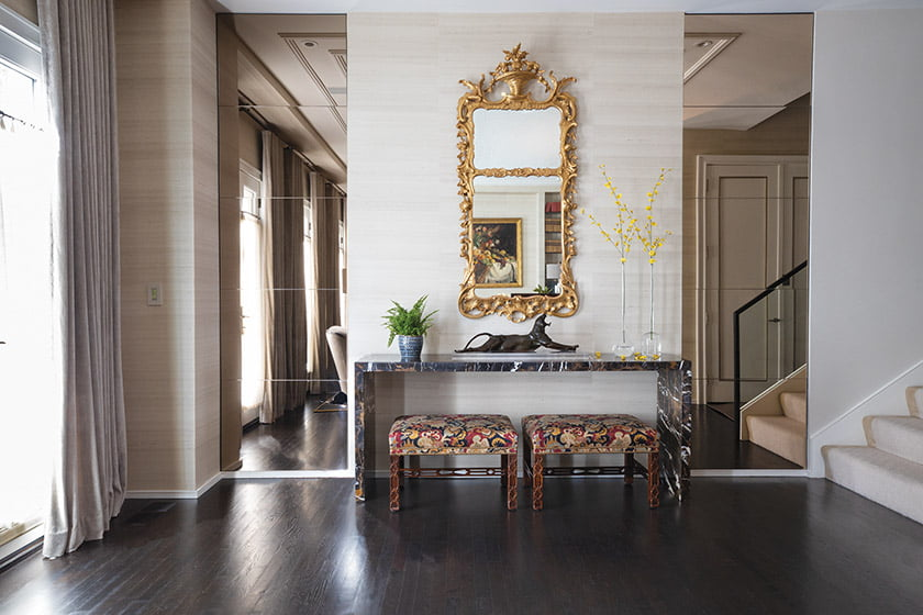A custom marble console designed by Solis Betancourt & Sherrill ushers guests into the foyer.