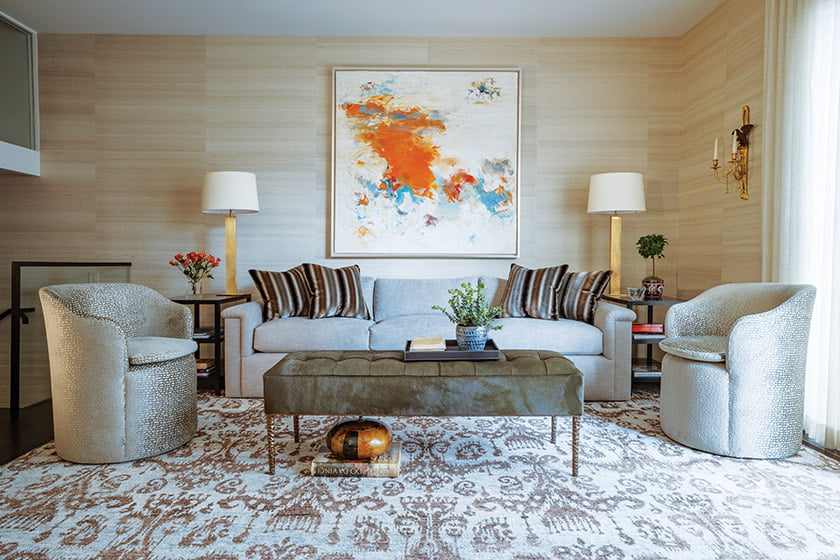 The family room marries a tufted-leather ottoman, swivel chairs in chenille and a painting from Merritt Gallery.