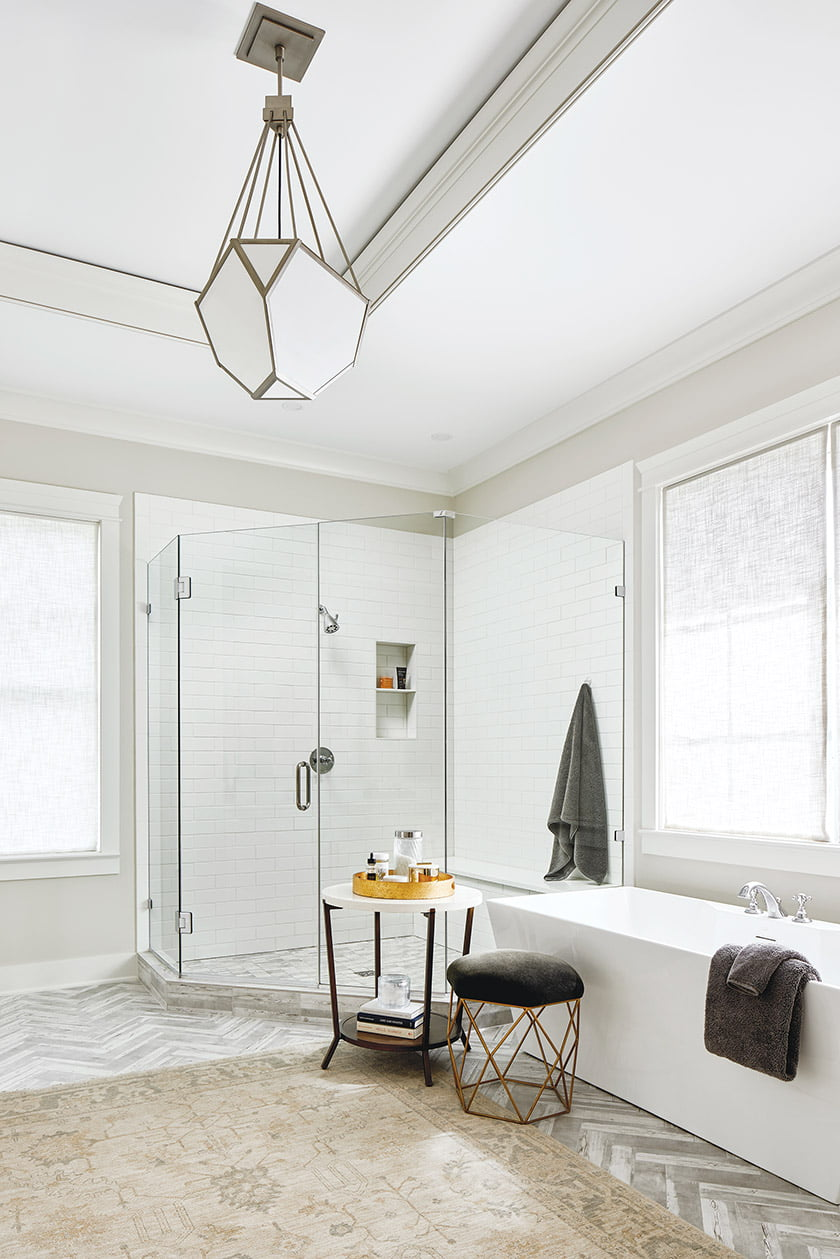 An Oushak rug softens the marble-tiled floor in the owners' bathroom.