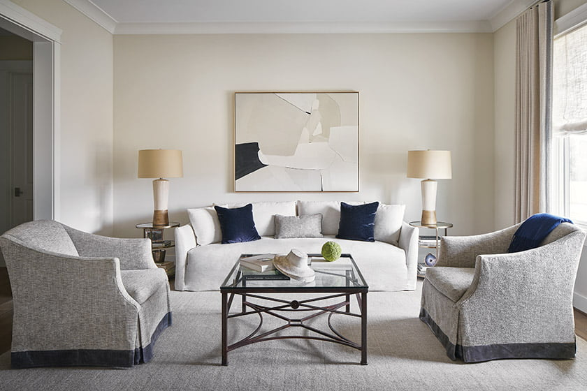 In the living room, antique-gold Arteriors tables and a Joelle Somero painting invigorate the neutral palette.