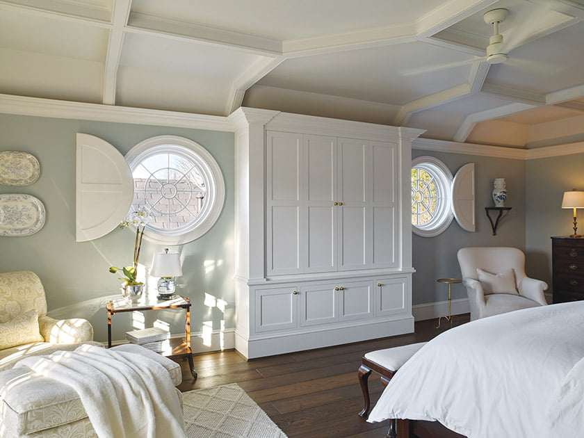 Shenandoah Shutters created custom plantation shutters to fit a bedroom's porthole-style windows. Photo: Darren Setlow Photography