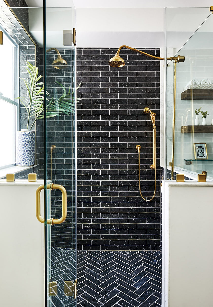Glazed navy brick in a running-bond pattern clads the owners' shower walls; a chevron motif covers the floor.