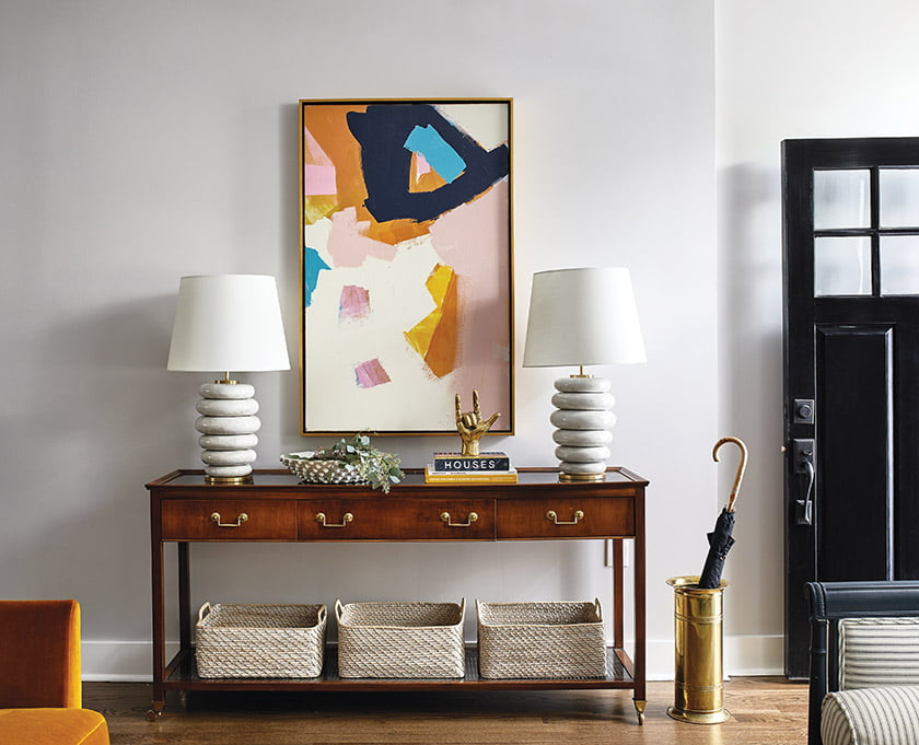 An abstract canvas by Jenny Prinn dominates the entry, flanked by Kelly Wearstler table lamps.
