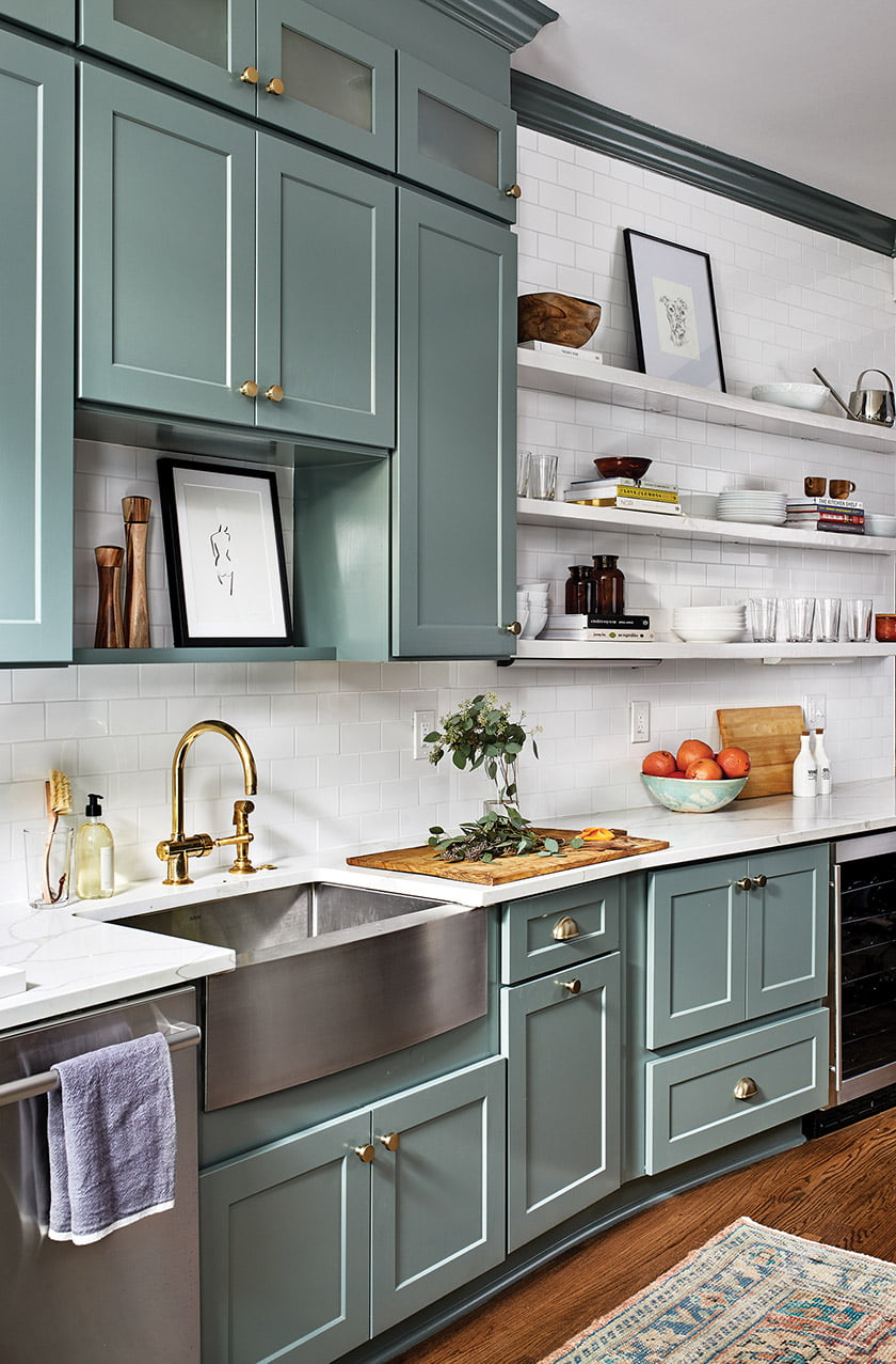 Cabinets painted in Farrow & Ball's Card Room Green and Waterworks subway tile add zest to the kitchen.