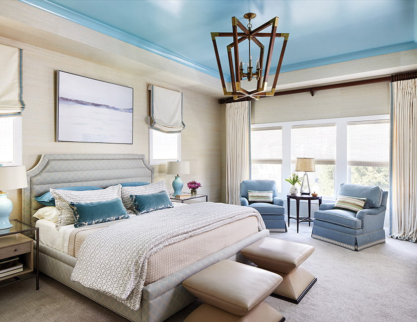 Phillip Jeffries wall covering provides a soothing backdrop in the owners' bedroom. Austin designed the bed and swivel chairs; the chandelier is from Currey & Co.