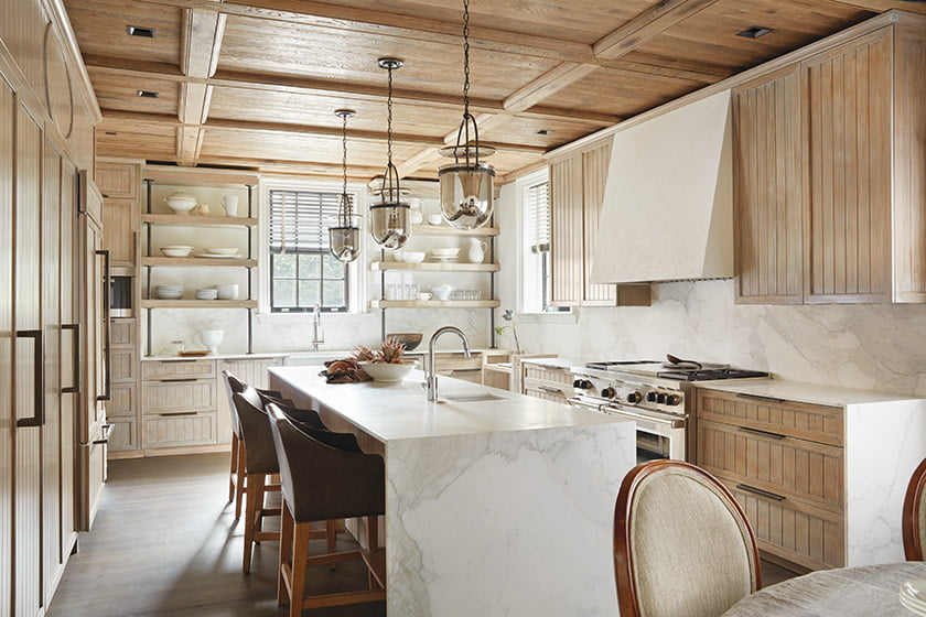 Patrick Sutton employed a palette of light-colored, tactile materials—from faux-bois custom cabinetry and soft-white Calacatta Gold marble countertops and backsplash to creamy lime-plaster walls to create the serene vibe the clients were after.
