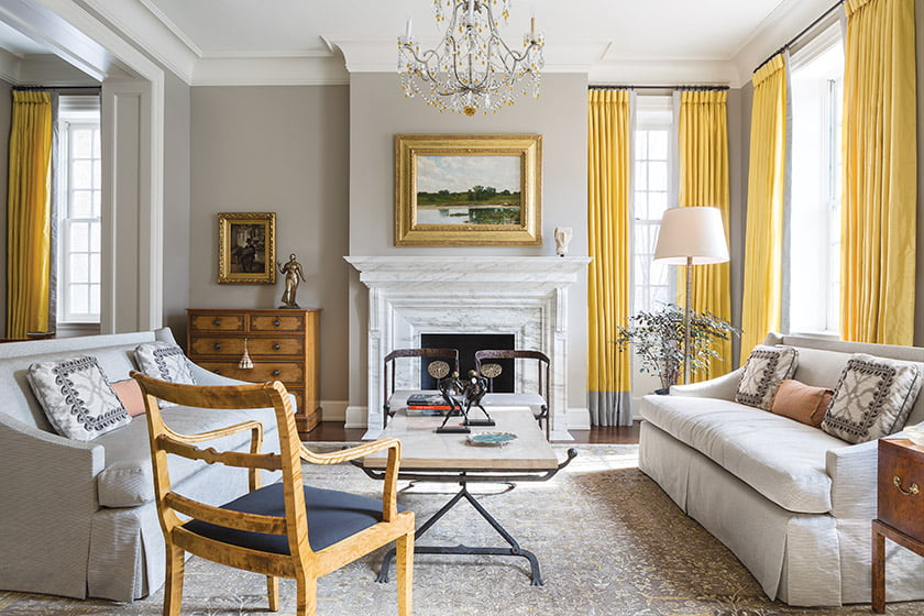 In the living space, Madeline Stuart sofas rest upon an antique rug; window panels, combining two Rose Cumming silks, up the sunshine quotient.