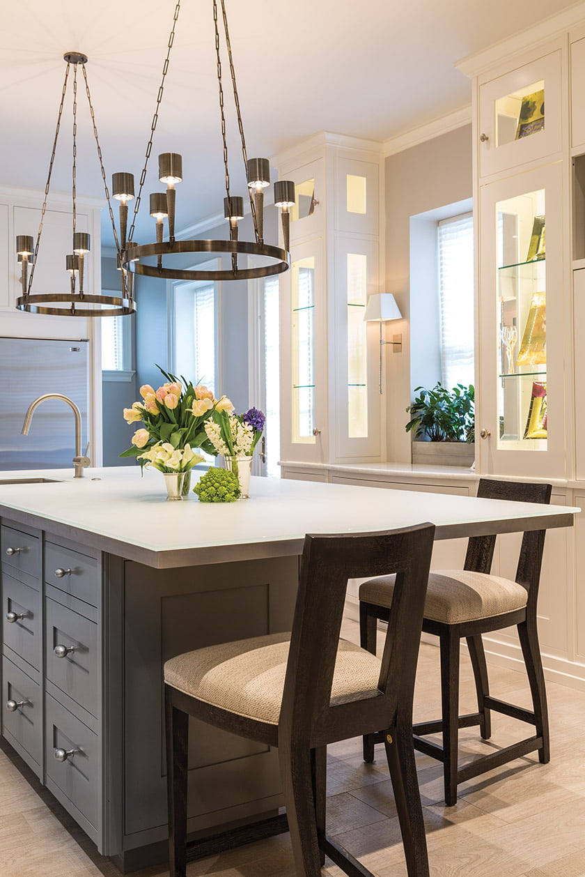 The kitchen island's etched-glass countertop reflects light from patinated-nickel chandeliers, designed by Jonathan Browning, hanging above.