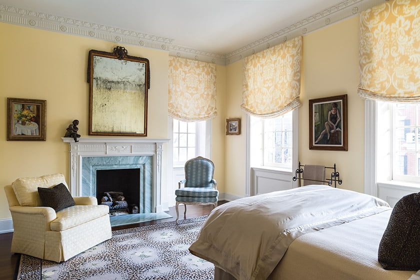The guest bedroom's existing architectural details, from the intricate crown molding to the classical fireplace mantel, provided an elegant envelope for furnishings culled from the owners' former home.
