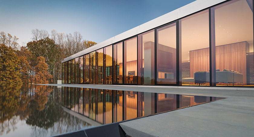 A cluster of volumes offers wide-open living spaces focused on exceptional views; a 105-foot-long lap pool  flows toward the Blue Ridge Mountains.