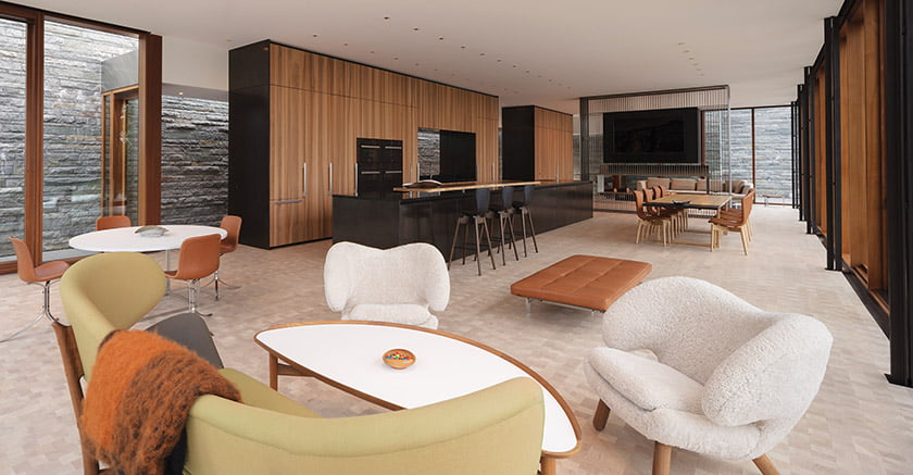 Stone is visible behind a module incorporating kitchen appliances and Boffi cabinetry set in furniture-quality walnut paneling.