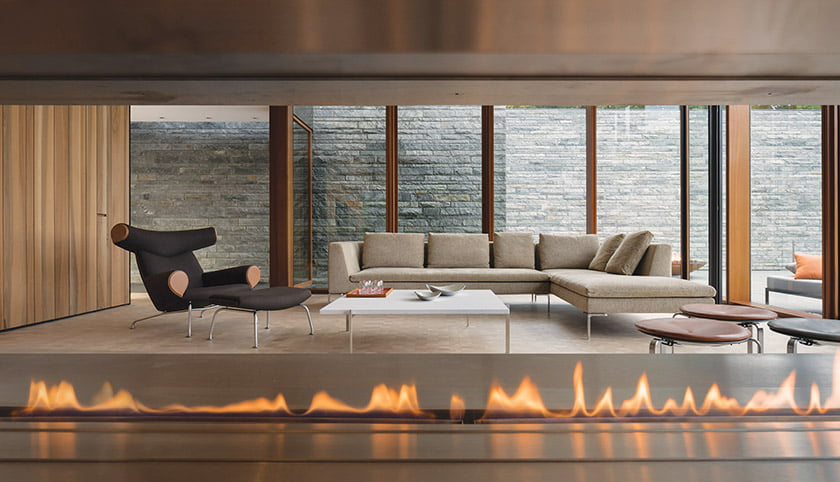 In the formal sitting area, a custom fireplace warms a B&B Italia sofa and Hans Wegner Ox chair.