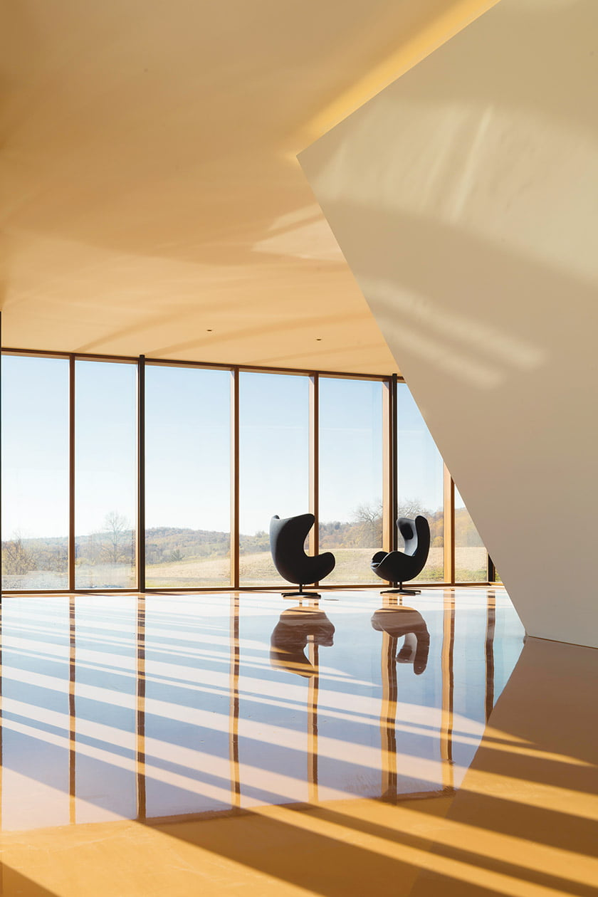 Arne Jacobsen Egg chairs take in 360-degree views in the upper-level aerie, where epoxy resin was poured over concrete.