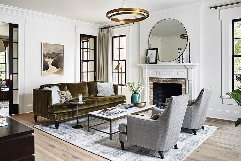 In the living room. a Room & Board sofa in moss-green velvet and gray side chairs are grouped under a Circa Lighting pendant; new pocket doors connect to the family room.
