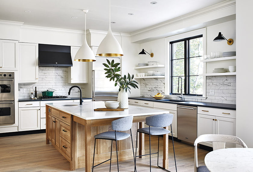 In the revamped kitchen, Benton designed a new natural-wood island with a prep sink; open shelves and sconces flank a new French casement window.