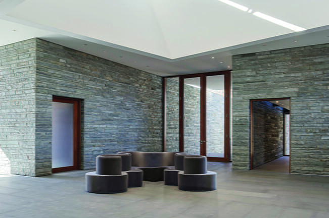 Stacked-stone walls define a 1,600-square-foot atrium, which serves as a covered porch, occasional event space and working-from-home office.