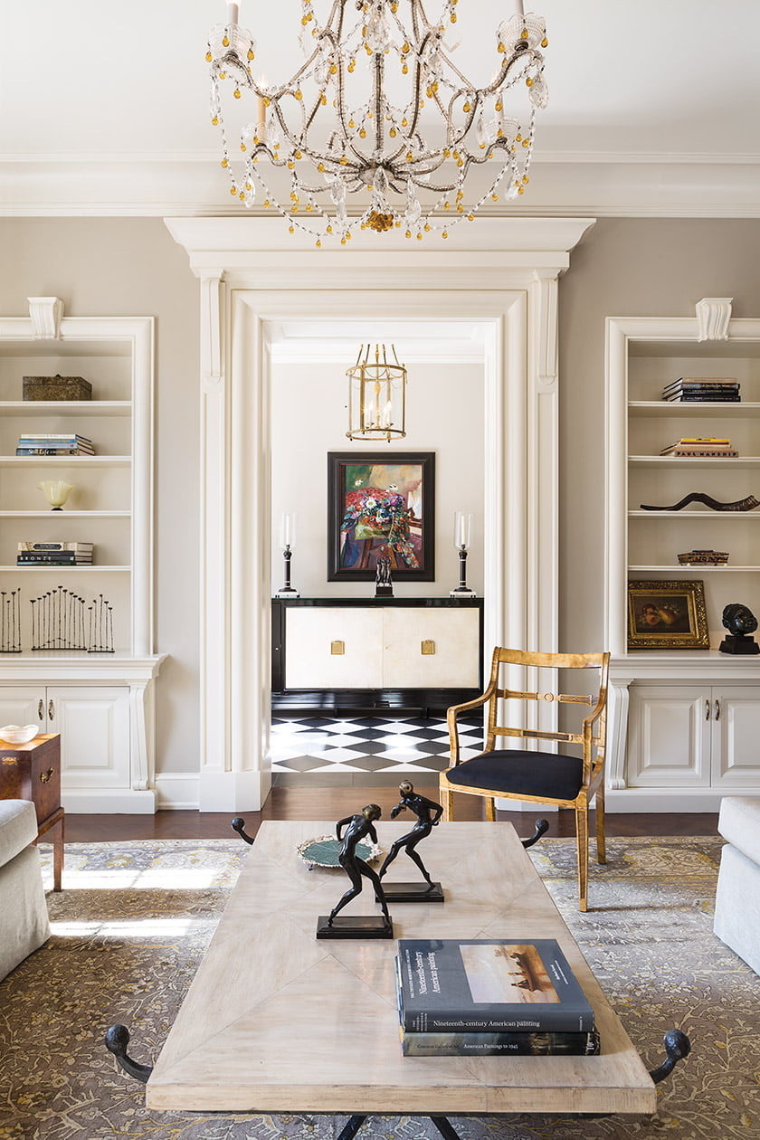 The front parlor connects to the entrance hall through a preserved cased opening, which frames an Art Deco cabinet that designer Fabiola Martens uncovered at New York-based Karl Kemp Antiques.
