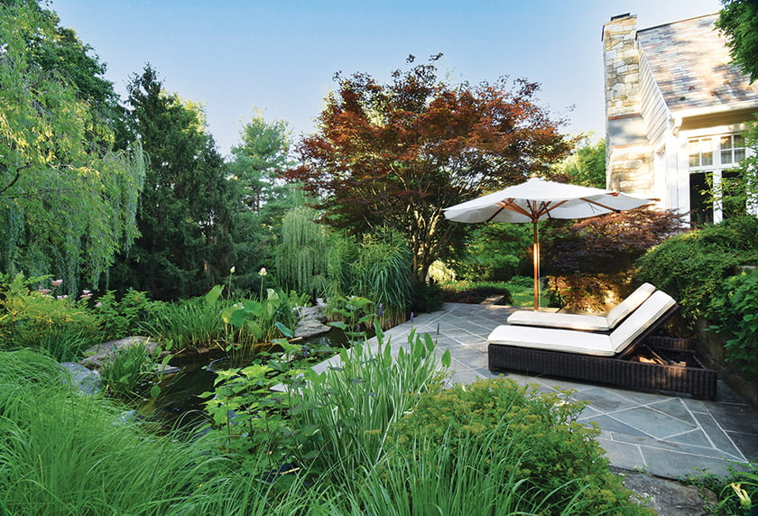 Comfortable seating on a small patio overlooks a koi pond.