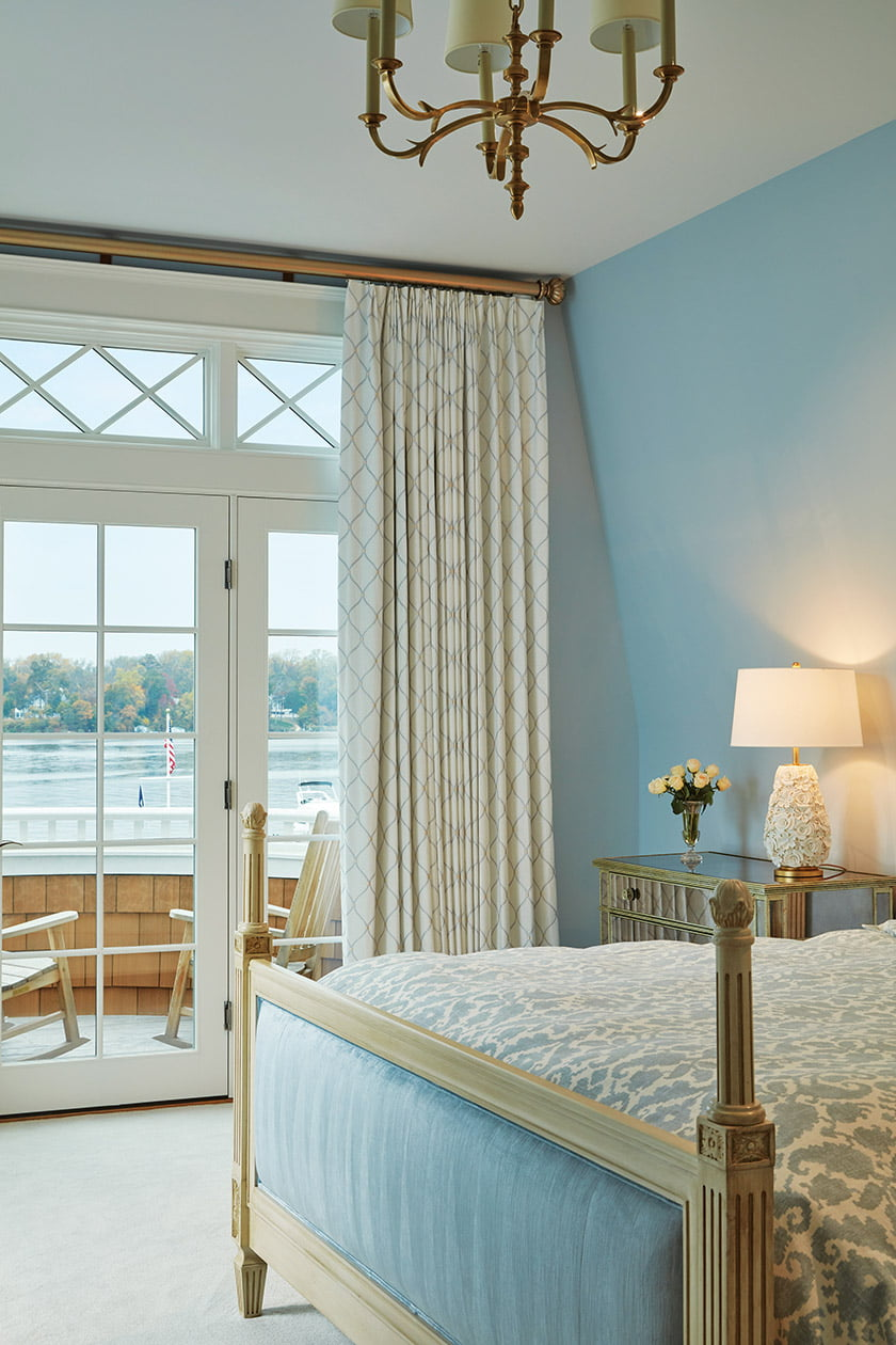 An upstairs guest bedroom opens to a curved balcony affording stellar river views. Photo: David Burroughs
