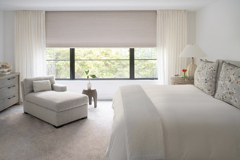 In the owners' tranquil bedroom, a custom chaise by O'Henry House invites repose; Conrad shades and Romo drapes fabricated by Jose Goncalves & Co. frame the window.