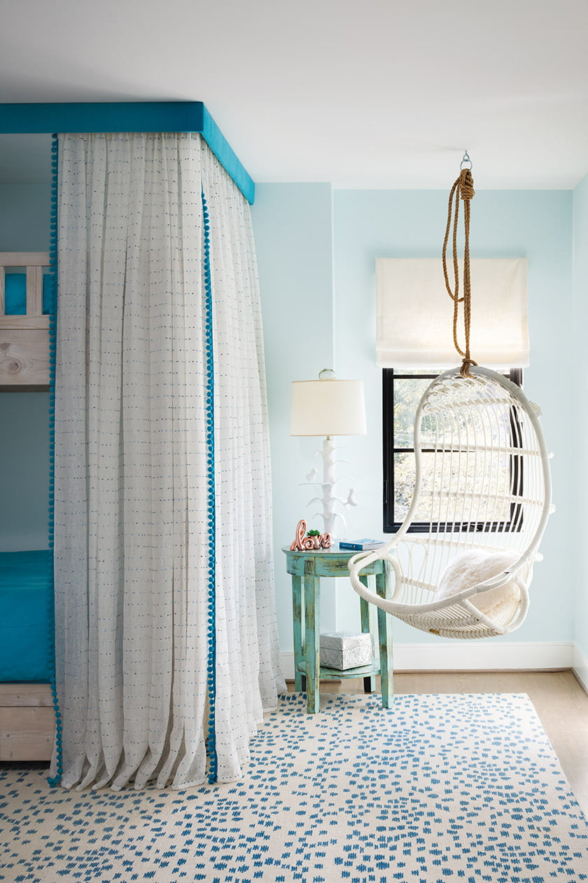 A daughter's playful bedroom boasts a Serena & Lily hanging chair; Kathryn Ireland sheers and Romo pompom trim adorn the bunk bed.