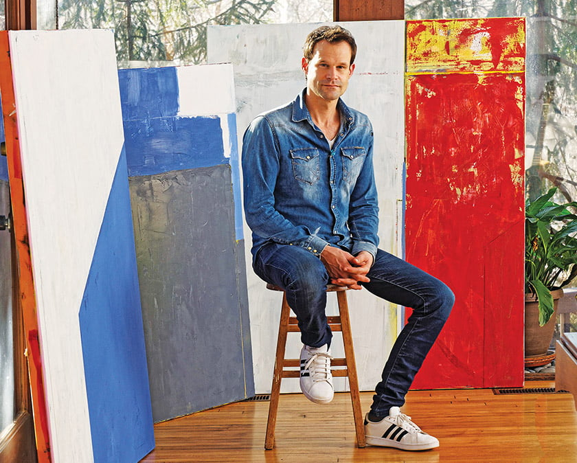 Framed by his bold paintings, Baer sits in the open living room  of his DC home.  Photo: Bob Narod