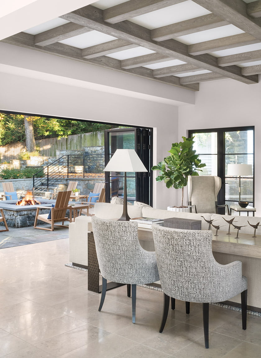 A NanaWall opens out to the patio. Marcali chairs pull up to a Gregorius Pineo console with a hammered-metal base.