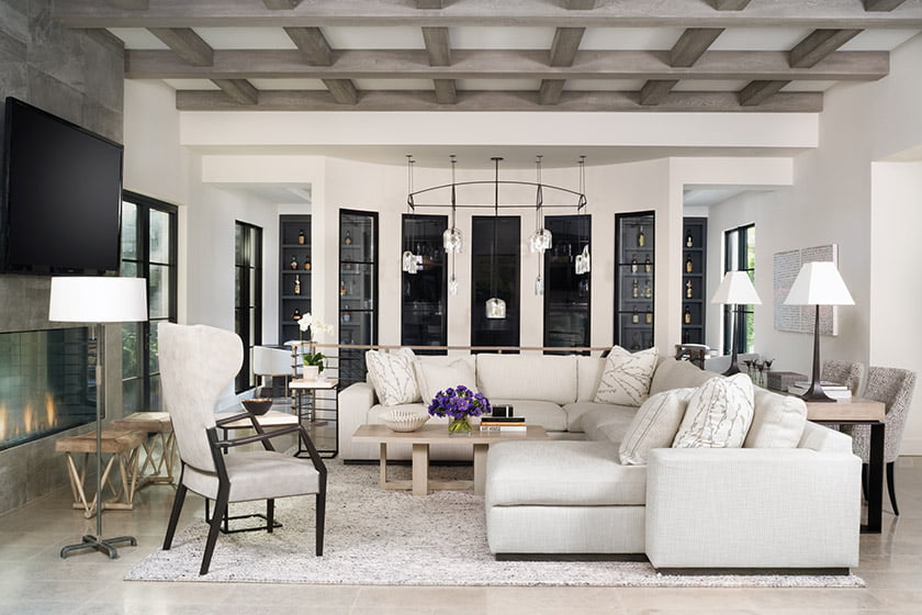 The family room combines an A. Rudin sectional, a contemporized wingback chair by Gregorius Pineo and a custom Paul Ferrante coffee table.