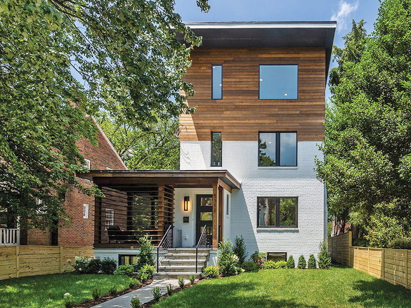 During a recent renovation of this 1940s-era home, the original brick was painted white and the porch and new third story were clad in Kebony siding.