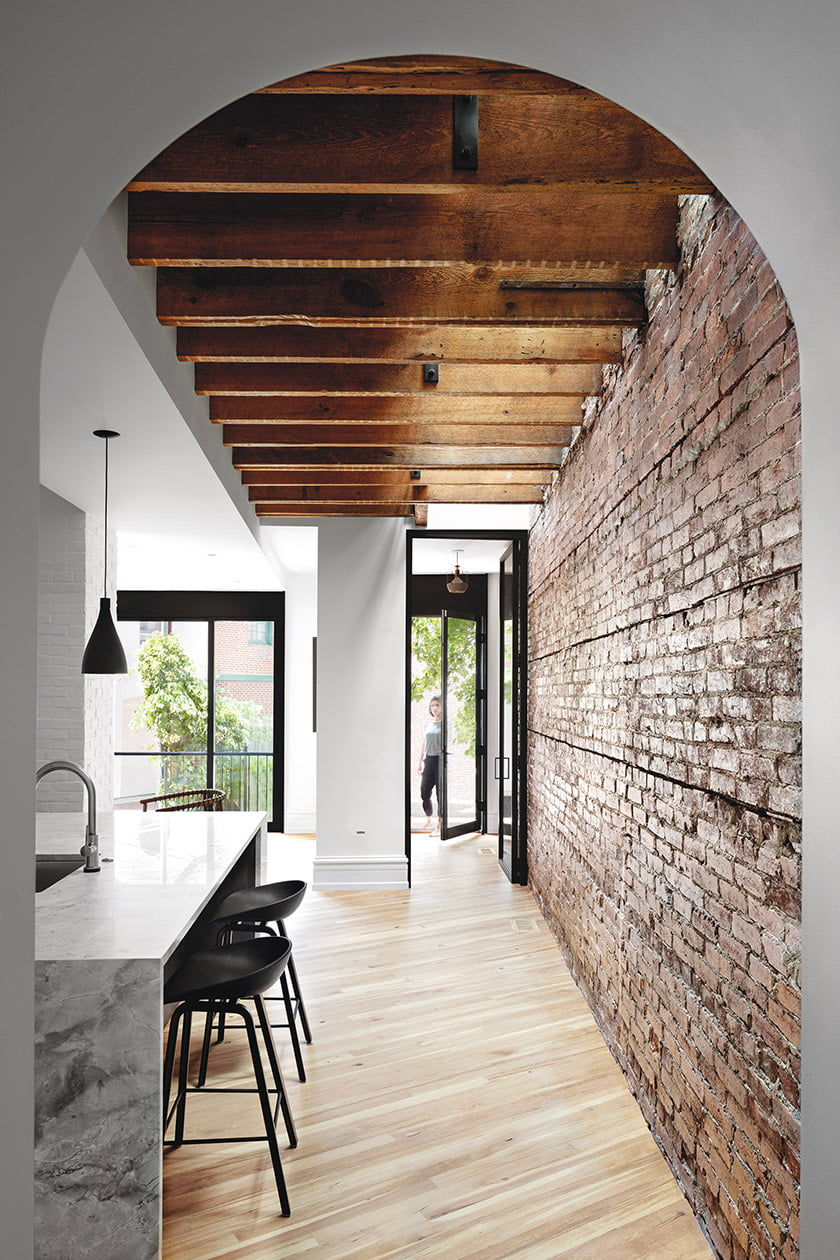 Ceiling joists are exposed on the main floor of the dogleg, where glass-and-metal doors lead to the backyard. © Jennifer Hughes