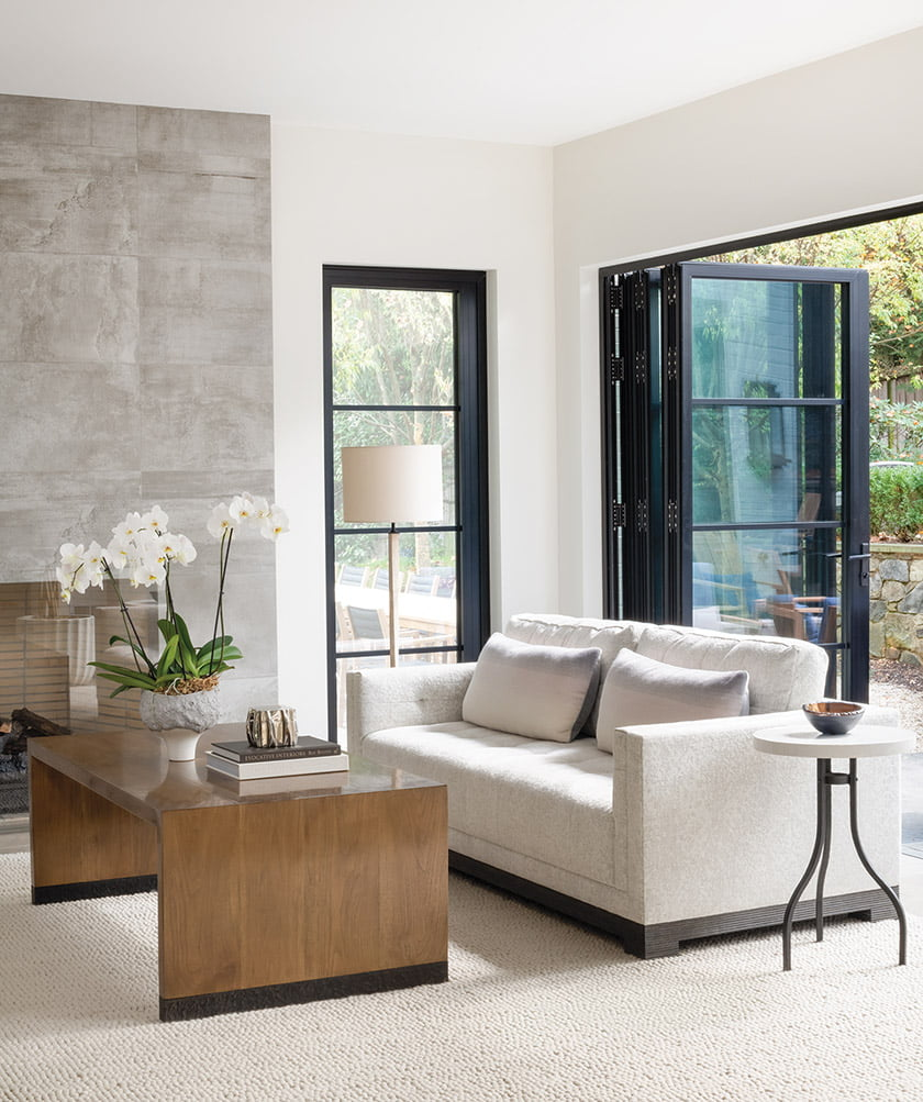 The living room features a Gregorius Pineo coffee table, a Holland & Sherry rug and an Ecocrete fireplace wall.