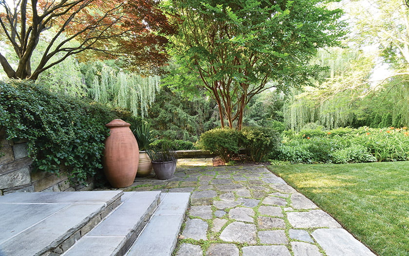 Mature plantings shade mossy flagstones.