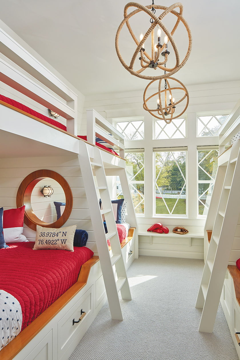 The nautical-themed bunkroom sleeps eight. Playful, porthole-like openings connect each pair of lower bunks. Photo: David Burroughs