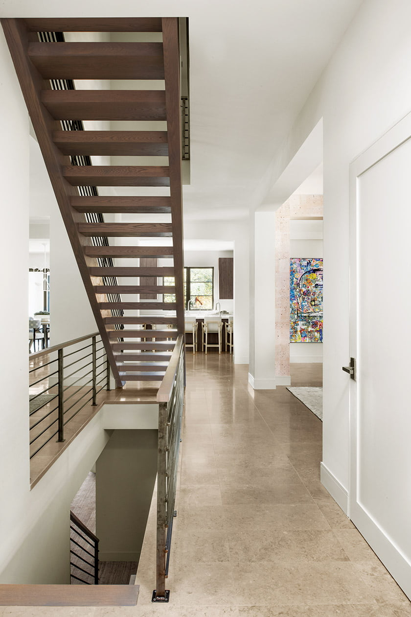 The main stair, with a view of the kitchen.