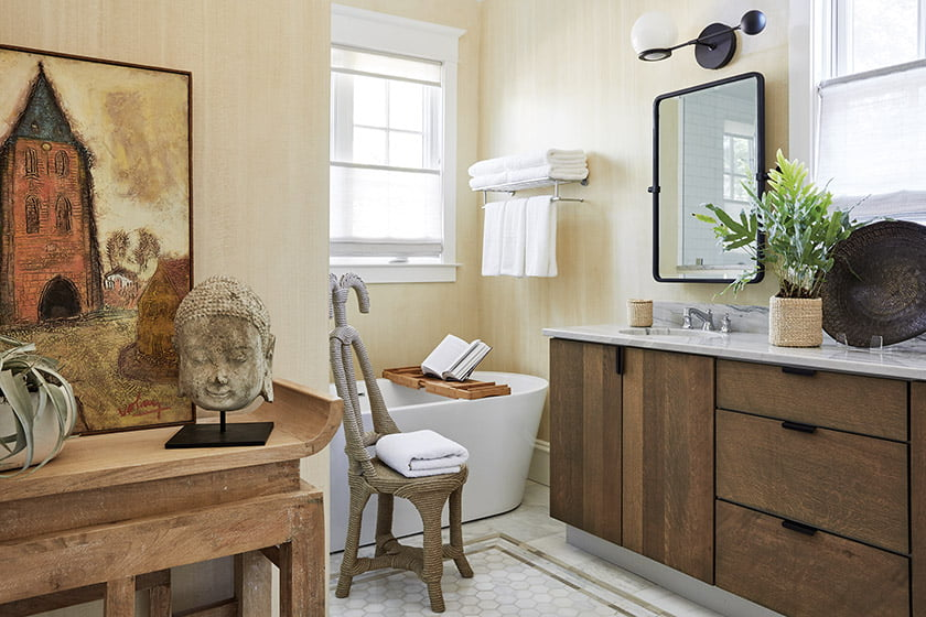 Resting on an antique altar table, a French painting and a smiling Buddha imbue the owners' bath with character.