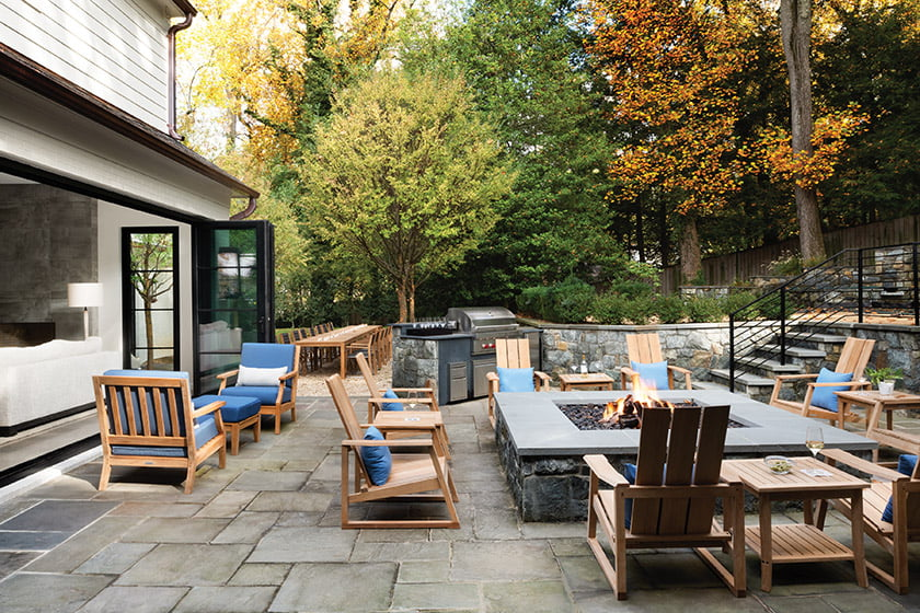 Seating abounds on the patio, where Country Casual Teak furniture gathers around a large fire pit.