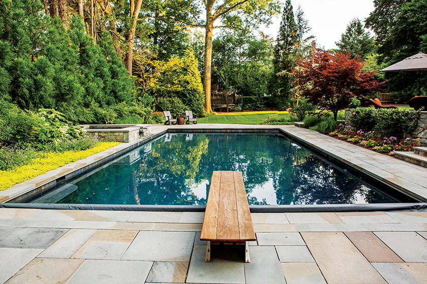 Pennsylvania flagstone borders pool with flowers and lush shrubbery
