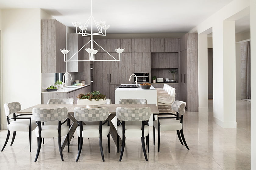 In the breakfast area, a Paul Ferrante chandelier hangs above a Keith Fritz dining table and Holly Hunt chairs.