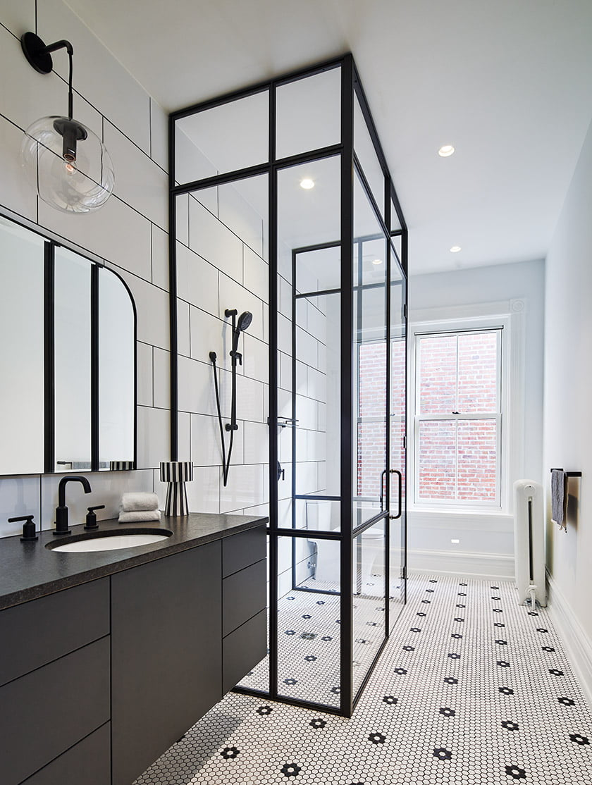 The hall bath showcases a steel-framed shower, large-format porcelain tile with black grout and mosaic floor tile. © Anice Hoachlander