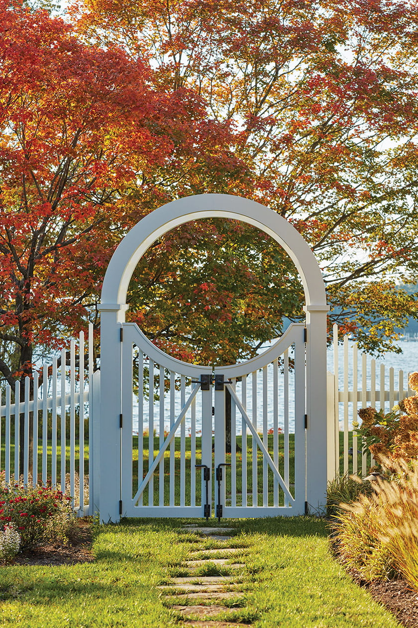 A white arbor and picket fence grace the side yard. Photo: David Burroughs