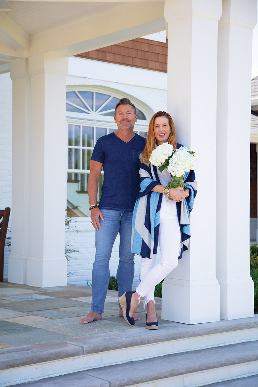Architect Chris Pattey and designer Erin Pitts pose beneath the front entry portico.