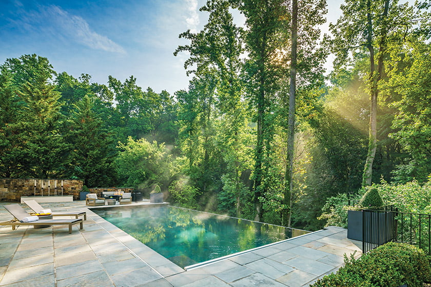 An aqua PebbleSheen finish plays up the reflections of the trees on the pool.