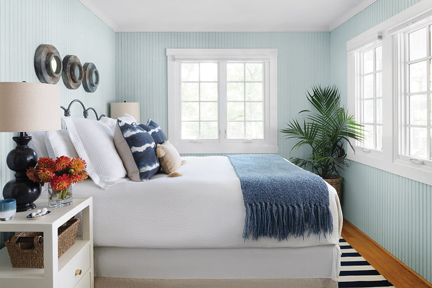 The main bedroom's original beadboard walls are finished in Fantasy Blue by Benjamin Moore. The striped rug is from Dash & Albert and the nightstands are by Made Goods.