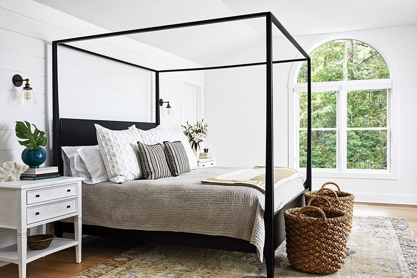 The second-floor owners' suite boasts an airy iron four-poster.